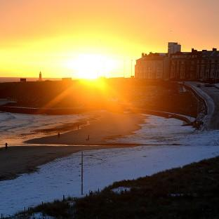 This Is Wiltshire: The sun rises over Tynemouth beach after a covering of snow.
