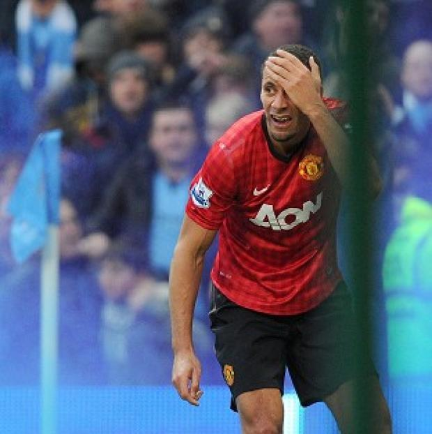 This Is Wiltshire: Manchester United's Rio Ferdinand holds his head after being hit by a coin at the Etihad Stadium