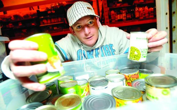This Is Wiltshire: Darren Clarkson with cans of food donated to the Swindon Foodbank