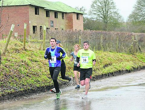Runners splash their way through the village of Imber