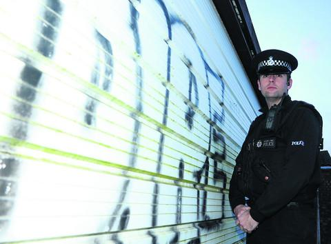 PC Keith McLaren examines some of the graffiti sprayed in Southampton Street