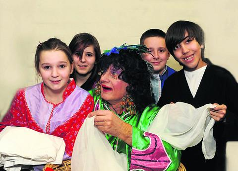 Dame Widow Twankey, played by Pete Grant, surrounded with the young laundry staff in Trowbridge Players'version of Aladdin