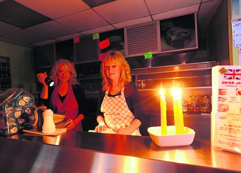 This Is Wiltshire: Light duties for Angie Willis, right, and Julie Whittaker, calling on candle power for serving up chips
