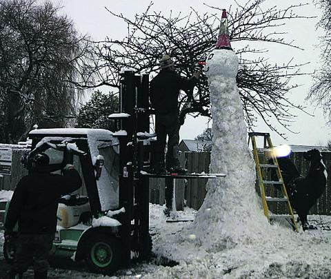 The 14ft tall snowman in the front yard of Acres Supply