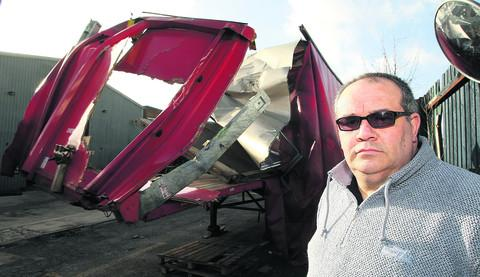 This Is Wiltshire: Jason Ellen, who owns Ellen Express Transport in Swindon, with the damaged lorry which crashed in Wootton Bassett Road bridge last week