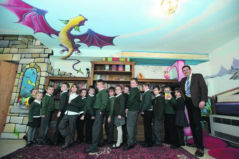 Holy Trinity head teacher Steve Heal with pupils in the library