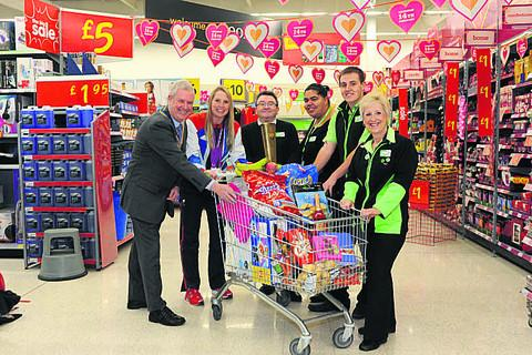 This Is Wiltshire: Paralympian Stephanie Millard helps Melksham Rotary president Warwick Allen and Asda staff Gary Salter, Naomi King, Matt Cameron and Kay Wallace to launch the Rotary Great Trolley Dash