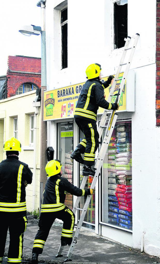 This Is Wiltshire: Fire crews at Baraka Groceries in Lagos Street, which has been damaged by fire