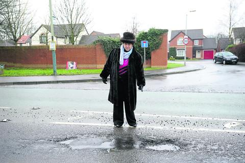 This Is Wiltshire: Coun Nina Phillips next to a pothole in Bristol Road, Chippenham