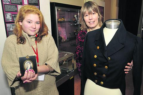 Curator Claire Lyall with volunteer Lucy Smith, left, and a coat belonging to mill owner John Plummer Clark and his portrait, from about 1820