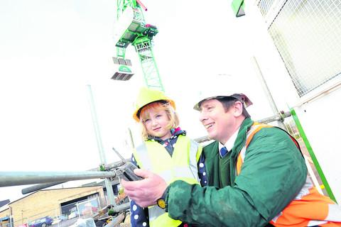 Amelia Boyd is shown how to operate the crane by McCarthy & Stone senior site manager Steve Reed