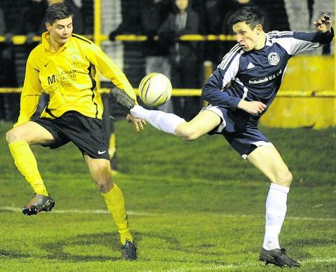 This Is Wiltshire: Melksham's Will Stead (yellow) loses out to a cheeky back-heel from Bradford's Steve Hulbert during Monday's Wiltshire Senior Cup quarter-final