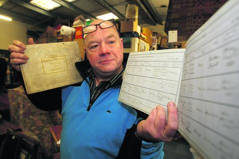 Craig Cook from Town Auctions with two baptism registers dating from the 1800s, which are due to be auctioned