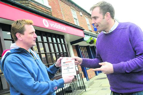 Justin Cook giving out a flyer to Greg Connor campaigning for Nodafone