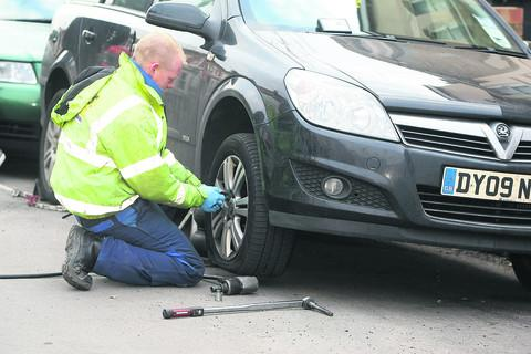 A mechanic attends to a slashed tyre in Dixon Street yesterday