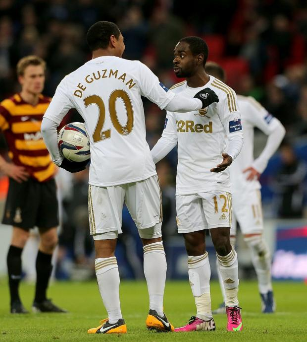 This Is Wiltshire: Nathan Dyer (right) debates with teammate Jonathan De Guzman over who wll take the Wembley penalty