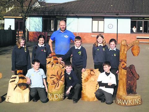 Chainsaw artist Andy Barton with King's Lodge Community School pupils Amelia, Ellery, Ayesha, Paul, Adam, Chloe, Orlando and Abbie