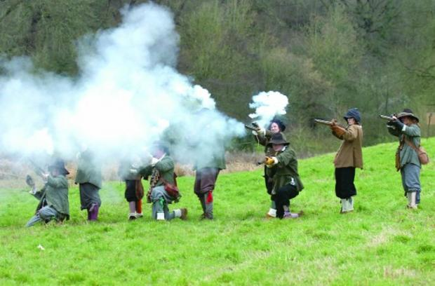 This Is Wiltshire: MUSKETEERS Shrouded in gunpowder, members of The Sealed Knot, the society of Cavaliers and Roundheads, recreate a scene from a Civil War battle