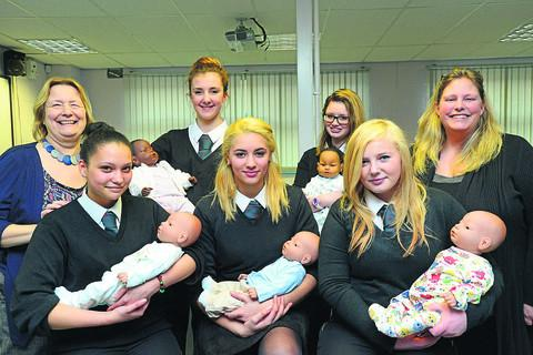 This Is Wiltshire: Royal Wootton Bassett Academy pupils Caylyn, Sasha, Joné, Milly and Lilly with their virtual babies. Included, left, community officer Linda Woodruffe, and right, student manager Kerry Heaphy			         picture by thomas kelsey