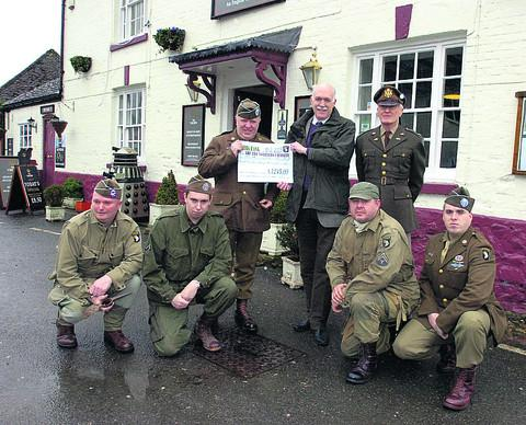 Colin Buckingham, Rob Stroud, Bruce Steggles, Richard Miller, from The Soldiers' Charity, Peter Davies, Tim Souch and Adam Ireland with a cheque for £1,245 from the summer march
