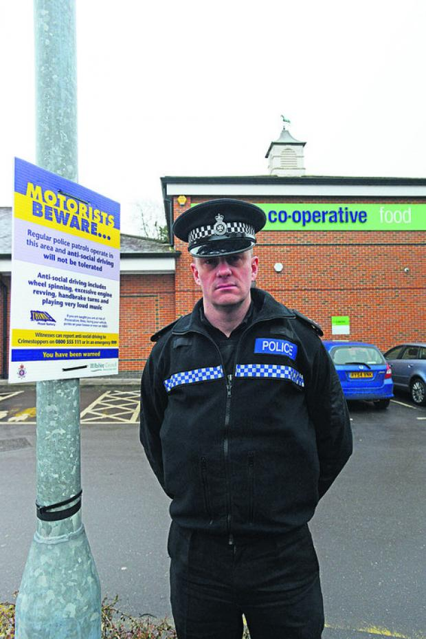 This Is Wiltshire: PC Richard Barrett with a warning notice at the Co-op car park