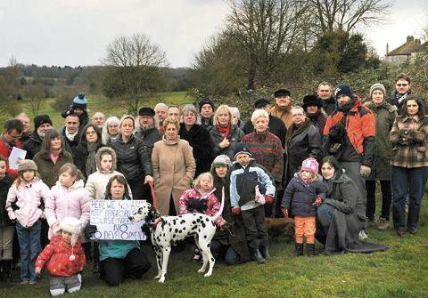 This Is Wiltshire: Marion Collett and fellow residents gather at the golf course to protest against development plans