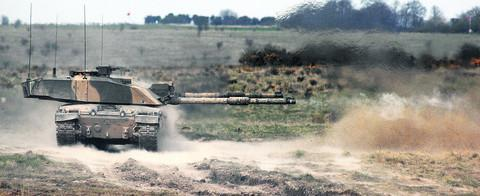 A Challenger 2 main battle tank fires a high explosive shell during a firepower demonstration held on ranges at Warminster