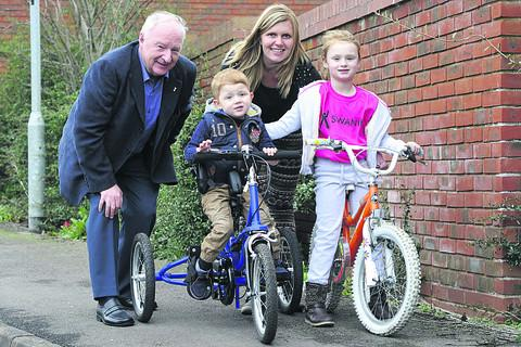 Three-year-old Lewis Blake out for a ride on his new trike, with mum Teresa, sister Izzy and Alan Waterson from the Ron Bryant Trust