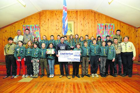 This Is Wiltshire: Tom Kinderman, a first responder with Shelterbox, receiving a cheque for £620, which Pewsey Scouts raised during a sponsored bike ride last