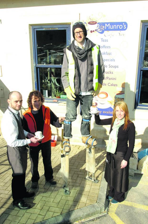 This Is Wiltshire: Phill Windley from Howlett-Neal Masonry on stilts with, from left, Alex Kelman from Cafe Munro, Stephen Howlett-Neal from the conservation firm and Bella Whittle from Munro's