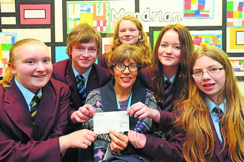 This Is Wiltshire: Diana Finch, CEO of Swindon Carers Centre, with pupils of Swindon Academy who raised money for Swindon Carers
