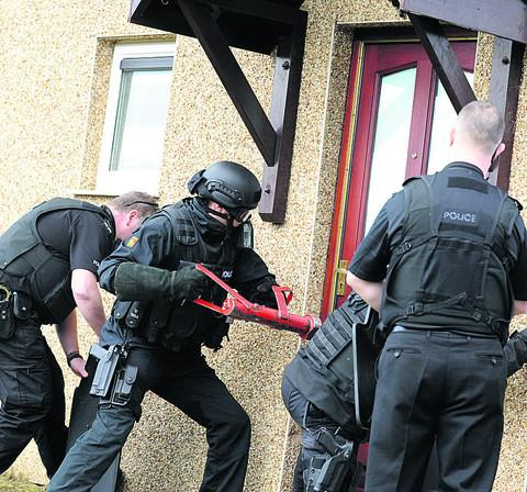 This Is Wiltshire: Police break down the door of an addess in Hungerdown Lane