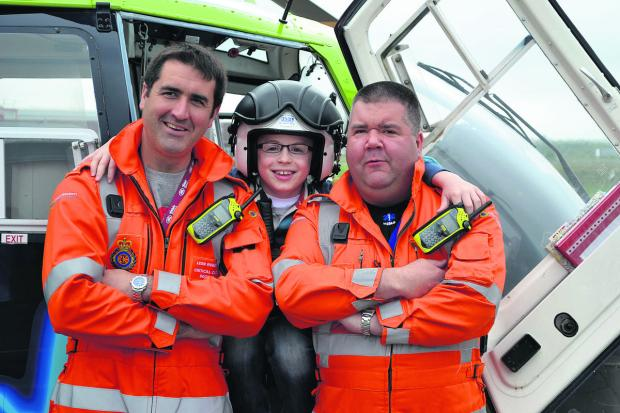 This Is Wiltshire: Max Deans, nine, with the Great Western Air Ambulance crew that saved his life. Max was knocked over by a bus in January in Haydon Wick