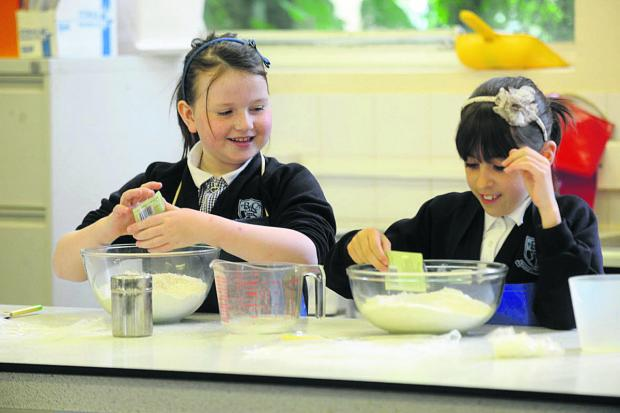 This Is Wiltshire: From left, Katherine and Fern of Bishop Cannings School test their culinary skills.