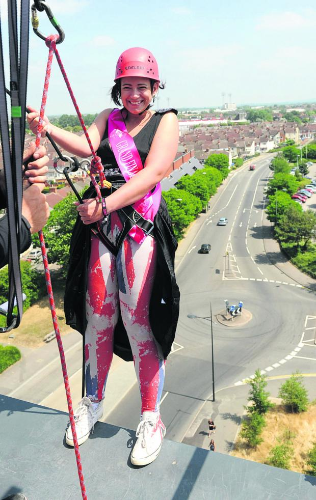 This Is Wiltshire: Former Miss Swindon and current Face of the Globe finalist Hannah Golding abseils for Prospect down the side of Jurys Inn