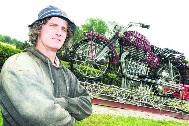 This Is Wiltshire: Toby Welsby with the giant motorcycle he has created to help publicise the Calne Bike Meet, which is being held this weekend