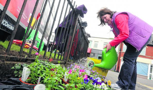 This Is Wiltshire: Members of the community cleaning up Old Town and planting flowers in April.