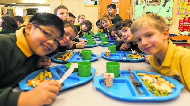 This Is Wiltshire: Pupils enjoying school dinners and below, Harrison gets his teeth into his favourite snack