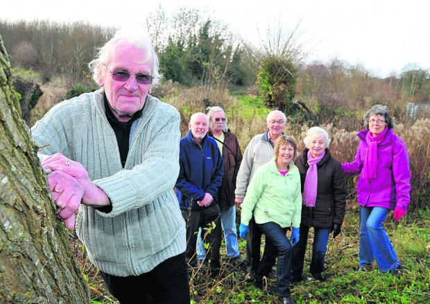 This Is Wiltshire: Wroughton Parish Council chairman Paul Hurst with councillors and campaigners who are raising money to buy Kings Farm Wood