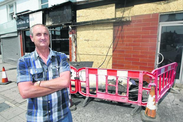 This Is Wiltshire: Peter Rogers, the owner of the Dream Lounge in Victoria Road, surveys the damage to the club after the fire