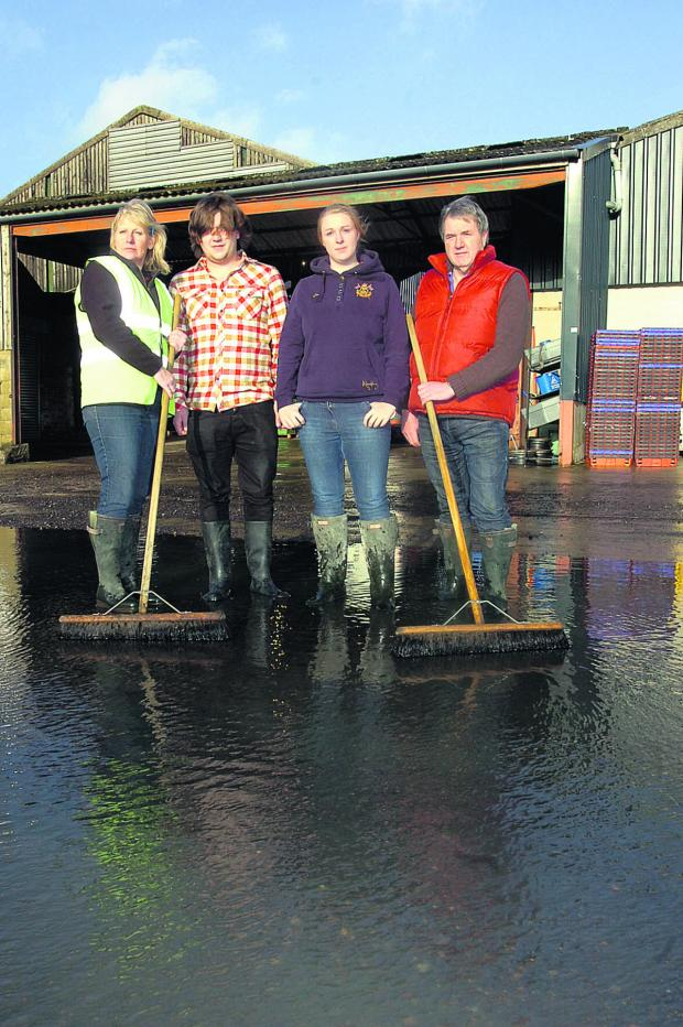 This Is Wiltshire: Kay Mortimer, Tom Edwards, Jesicca Bank and Ken Mortimer mop up after the flood