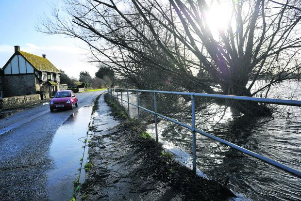 This Is Wiltshire: A motorist proceeds with  caution as rainwater threatens to flood a road near Cricklade