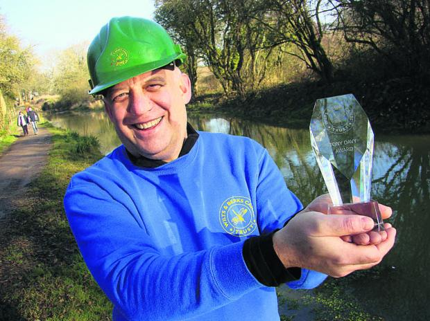 This Is Wiltshire: Branch chairman Derek Flexer holds aloft the Wilts and Berks Canal Trust's Tony Davy Award