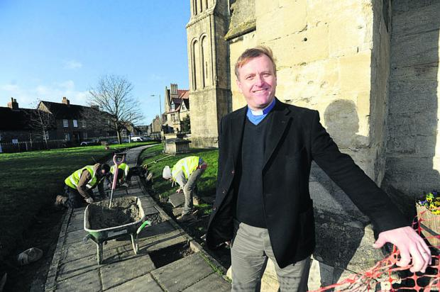 This Is Wiltshire: The Rev Neill Archer is pleased with repairs being carried out to paving at Malmesbu