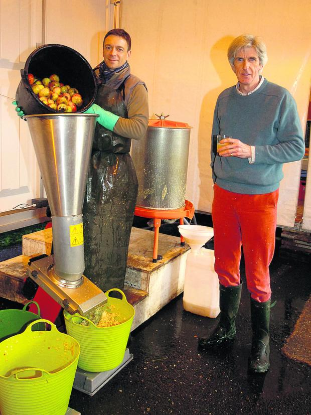 This Is Wiltshire: Robin Shatlock, left, at the juicer, helps Richard Paget, who runs My Apple Juice                                           (PM948) By paul morris