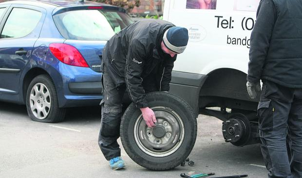 This Is Wiltshire: Andy Noton changes a tyre in Dixon Street after hundreds of were slashed overnight on cars and vans in the Old Town area last February