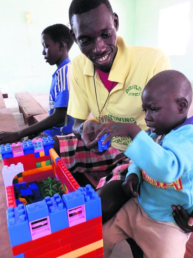 This Is Wiltshire: A child in Gunjur gets to grips with the toys on offer helped by a worker from Disabled Africa