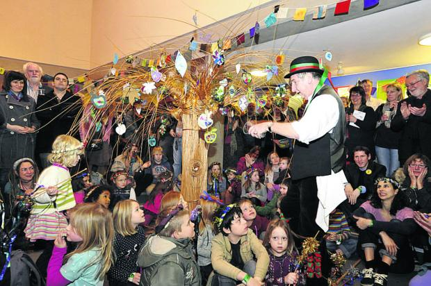 This Is Wiltshire: Holt Morris man Bryan Baker completes the Wassail ceremony by pouring cider on the tree at the second Bradford Roots Music Festival