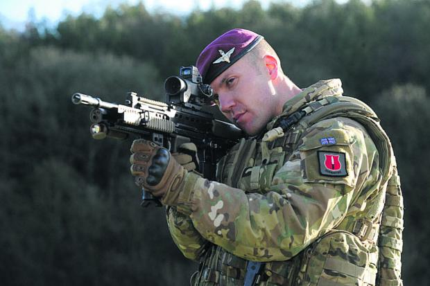 This Is Wiltshire: Major Nick French demonstrates the new laser light module on the SA 80 A2 gun