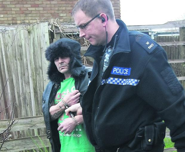This Is Wiltshire: An arrested man is led away by police after a drugs raid in Toothill
